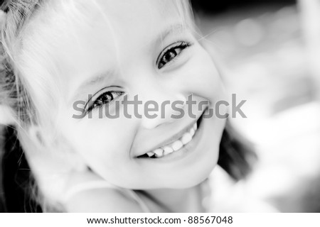 little girl smiling in a park close-up - stock photo