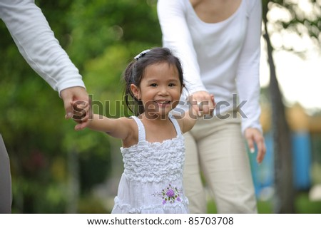 Little girl smiling in the park while with parents - stock photo