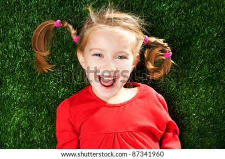 little girl smiling on a green lawn