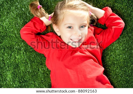 little girl smiling on a green lawn - stock photo