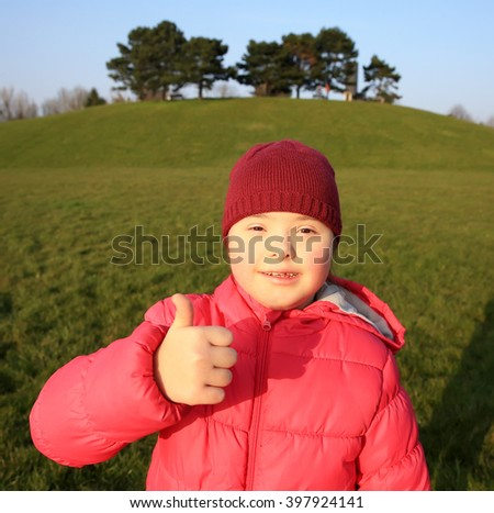 Little girl smiling on background of the green grass - stock photo