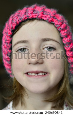 Little girl smiling portrait missing front tooth with winter hat - stock photo