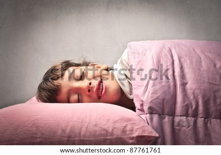 Little girl smiling while sleeping - stock photo