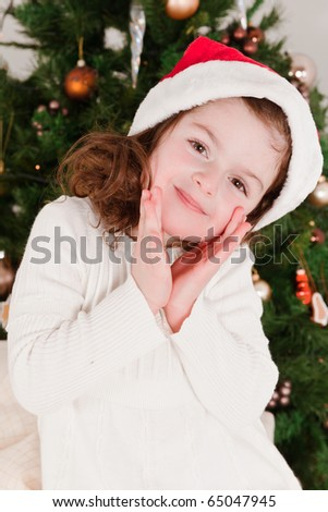 Little girl smiling with Santa Claus-hat in her head in a front of Christmas-tree - stock photo