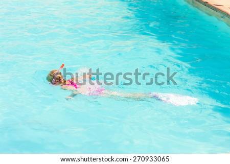 little girl snorkeling in swimming pool - stock photo