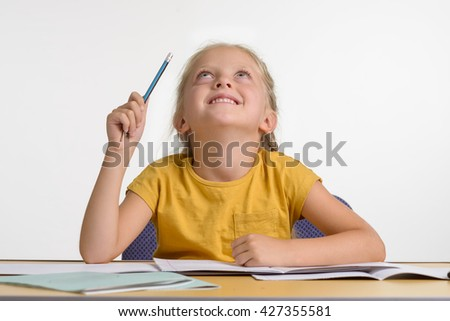 Little girl solved a problem in maths. Happy child after successful learning process. Baby got an idea. Kid looks upwards and smiles. A pencil in small hand is rised.