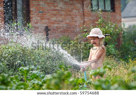 Little girl splashes from hose in garden