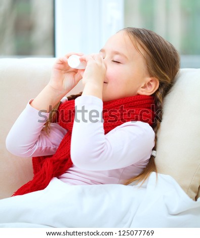 Little girl spraying her nose with nasal spray while sitting on sofa - stock photo