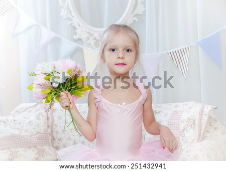 Little girl stand with flowers  in pink dress - stock photo