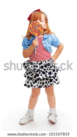Little girl standing and enjoying lollipop that hides her face - stock photo