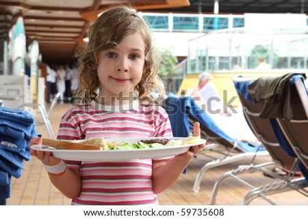 little girl standing and holding tray with food on cruise liner deck, half body - stock photo