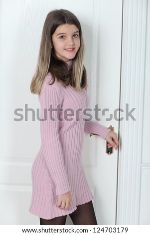 Little girl standing at the white door closed - stock photo