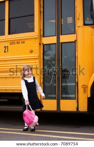 Little girl standing by a big school bus door with her pink backpack.