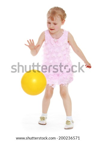 little girl standing in a short dress and playing ball. Isolated on white background