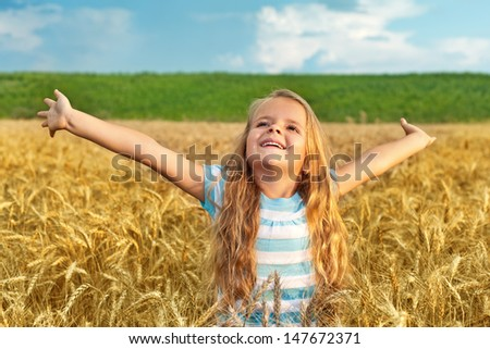 Little girl standing in wheat field with arms spread - late afternoon lights - stock photo