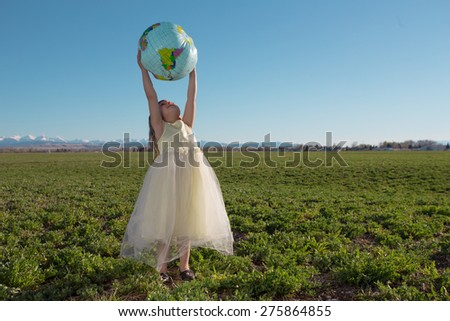 Little girl standing looking at globe in a farm field. - stock photo