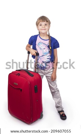 Little girl standing near the suitcase over white background  - travel or vacation concept  - stock photo
