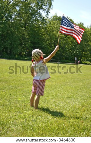 little girl standing on a lawn with USA flag in her hand - stock photo