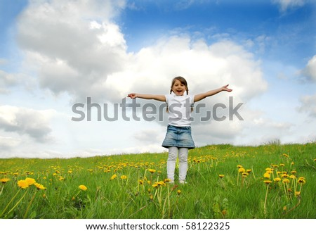 Little girl standing on a meadow in a field of beautiful flower - stock photo