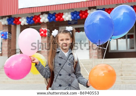 Little girl standing outdoor with color balloons in hands. - stock photo