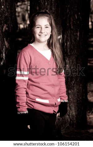 Little girl standing outside in a park - stock photo