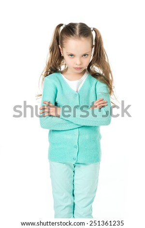 little girl standing with a serious, stubborn, frustrated expression on his face - stock photo