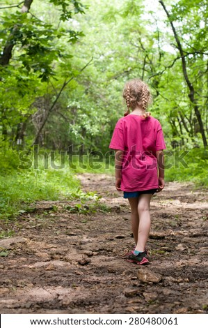 Little Girl Stands Alone On A Beautiful Forest Path - stock photo