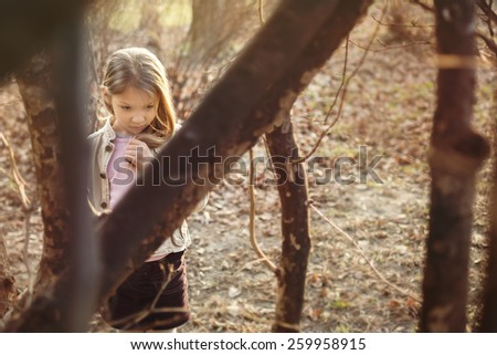 Little girl stands among the trees and with a sad expression on her face looking down. - stock photo