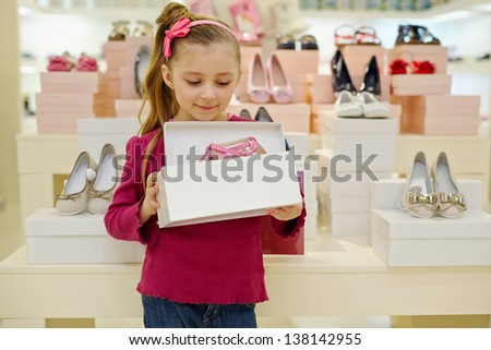 Little girl stands and holds open box with pink shoes in shoe store - stock photo