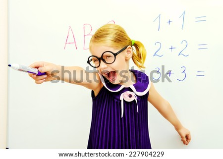 Little girl stands at the blackboard, points her finger and shouts. Educational concept. - stock photo