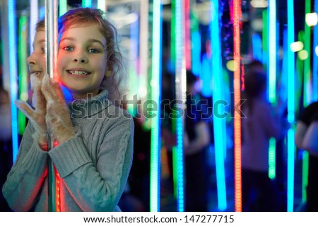 Little girl stands in mirror labyrinth illuminated with color lights - stock photo