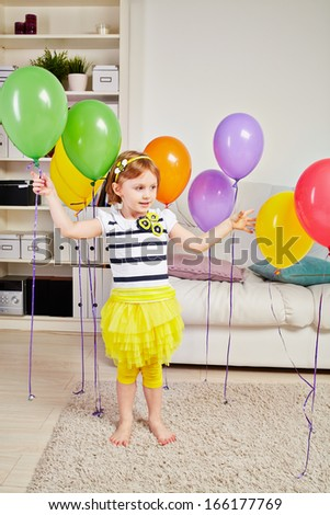 Little girl stands in room on light carpet on floor and touches birthday air balloons