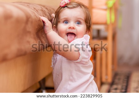 little girl stands near the sofa at home