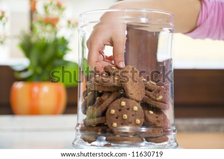little girl stealing some cookies from the jar - stock photo