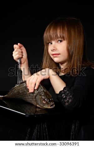little girl sticks fork into raw fish - stock photo