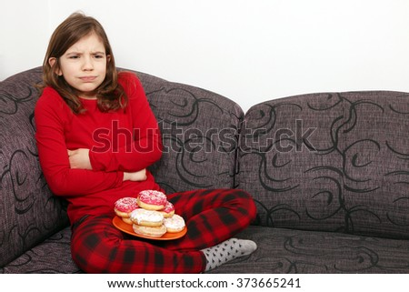little girl stomach ache because he ate a lot of donuts - stock photo