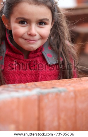Little girl stood by brick wall - stock photo