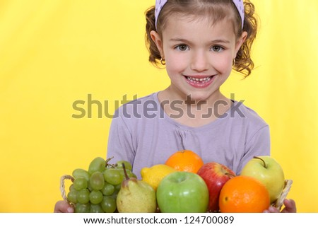 Little girl stood with fruit