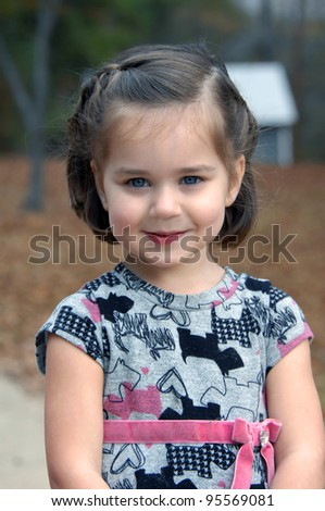 Little girl stops in her playing to smile. She is playing outdoors in rural area. - stock photo