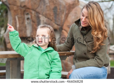 Little girl storytelling to her mom on a bench at the park - stock photo