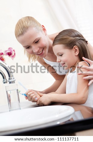 Little girl studies how to clean teeth with her mum