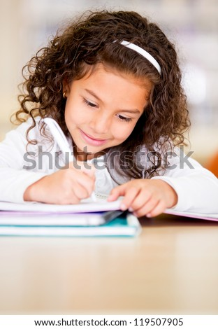 Little girl studying at the library looking happy - stock photo