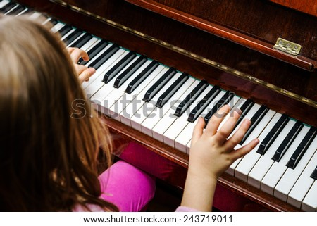 Little girl studying to play the piano at home - stock photo