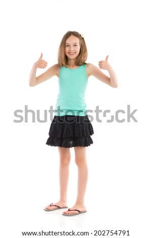 Little girl success. Young girl in teal shirt and black skirt showing thumbs up. Full length studio shot isolated on white. - stock photo