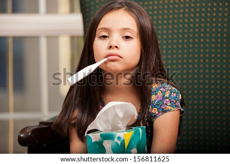 Little girl suffering from a cold, holding a box of tissues and a thermometer in her mouth - stock photo