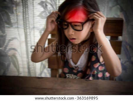 Little girl suffering from headache and holding hands on her head.Blurred - stock photo