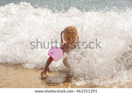 Little girl summer fun in the sea wave at sand beach.