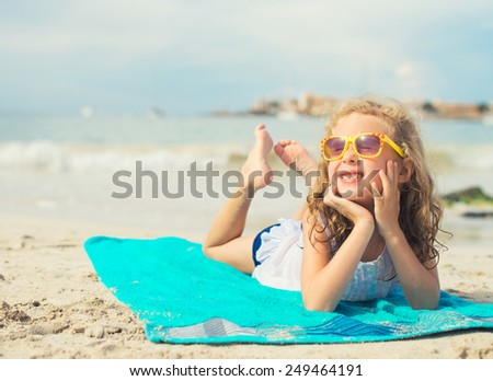 Little girl sunbathing on the beach. Place for text. - stock photo