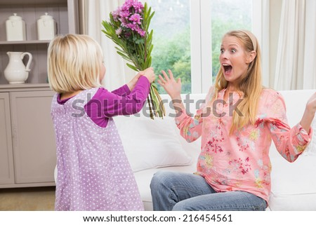 Little girl surprising her mother with flowers at home in the living room - stock photo