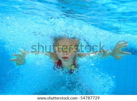 Little girl swim underwater in pool. - stock photo